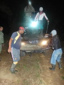 Para kru berburu meletakkan babi hutan di atas garda mobil berburu.