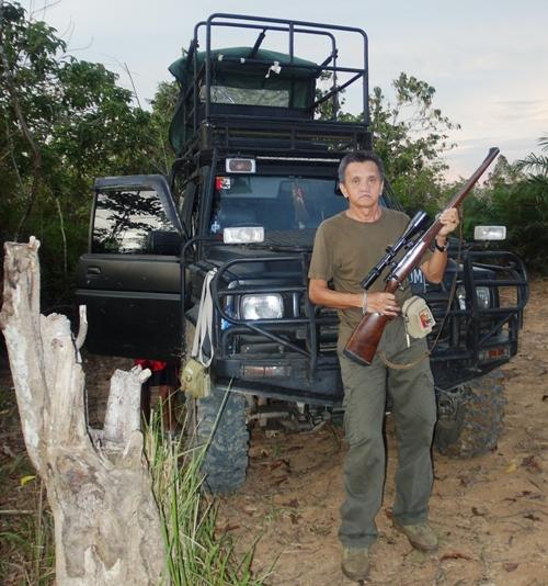 Gaya hunter John Natalie saat berpose di depan mobil berburu.